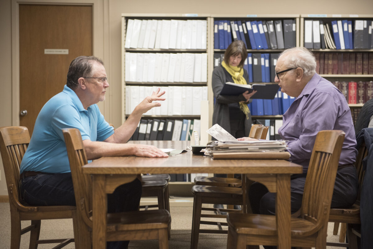 Two men in the research center talking to one another