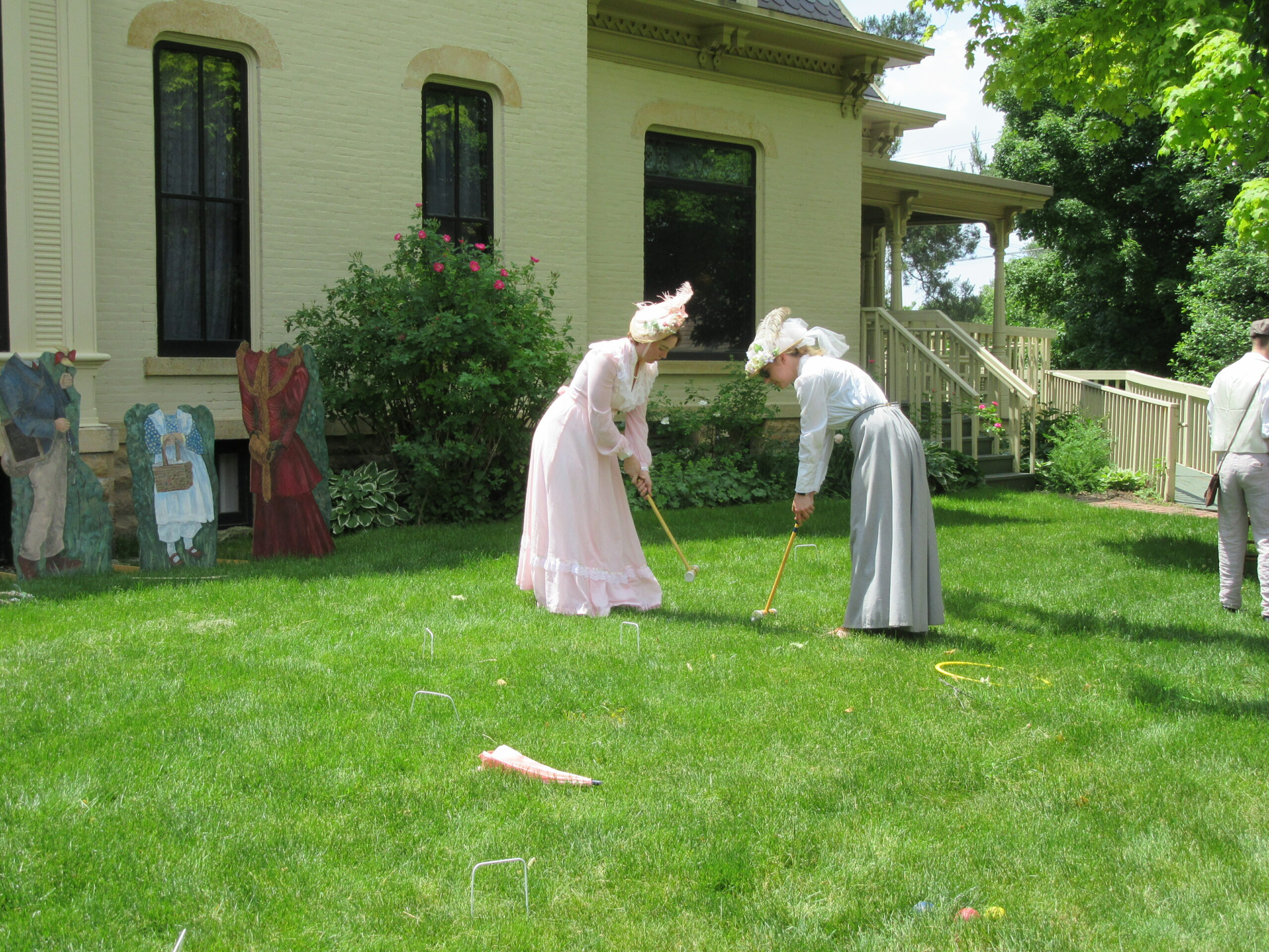 Ladies playing croquet at a past Victorian Lawn Party