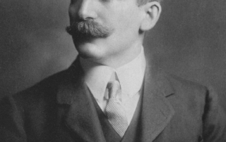 Sir henry Wellcome in a black and white image wearing a coat and tie with a mustache