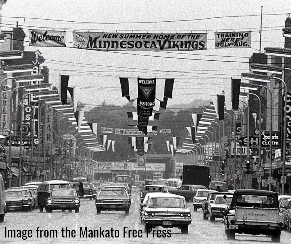 Vikings Training Camp banner on Front Street with cars, black and white image