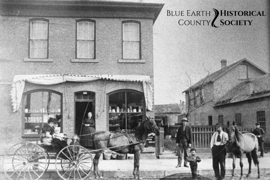 Enfield's Grocery Store building with a horse drawn cart and people in front. black and white image